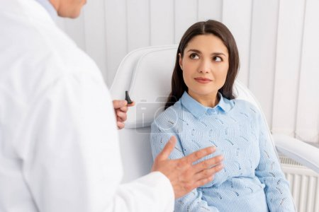 Photo for Cropped view of otolaryngologist talking to attractive patient while holding ear speculum - Royalty Free Image