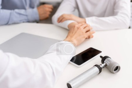 Photo for Cropped view of otolaryngologist touching hand of child near otoscope and smartphone with blank screen - Royalty Free Image