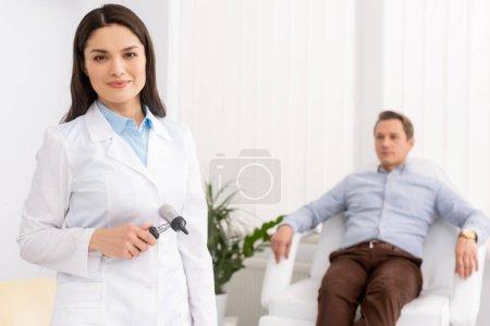 Photo pour Foyer sélectif d'attrayant médecin souriant à la caméra près beau patient assis dans une chaise médicale - image libre de droit