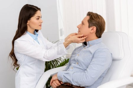 Photo for Beautiful, attentive ent physician examining handsome patient in clinic - Royalty Free Image