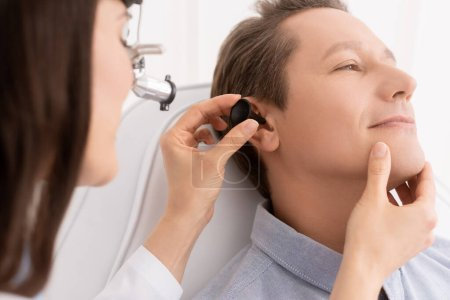 Photo for Cropped view of otolaryngologist in ent headlight examining ear of handsome patient - Royalty Free Image