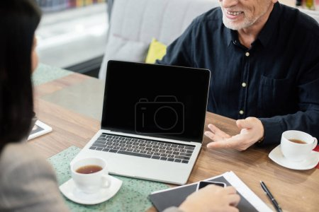 Photo for Cropped view of smiling businessman talking with businesswoman and sitting near laptop during business meeting - Royalty Free Image