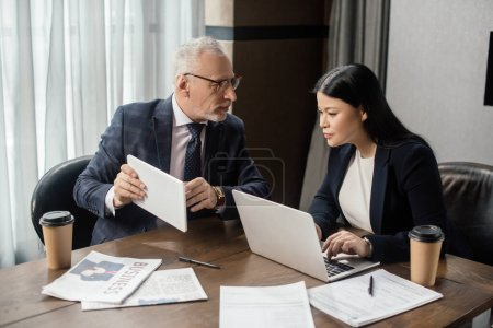 businessman showing digital tablet to asian businesswoman during business meeting