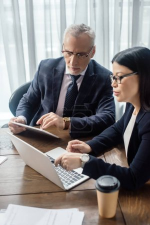 Photo pour Homme d'affaires et asiatique femme d'affaires regardant ordinateur portable et parler pendant la réunion d'affaires - image libre de droit