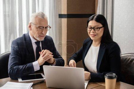 Photo pour Un homme d'affaires et une femme d'affaires asiatique souriante regardent un ordinateur portable pendant une réunion d'affaires - image libre de droit