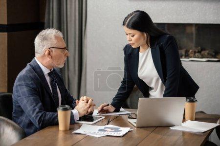 Photo pour Homme d'affaires parler avec asiatique femme d'affaires lors d'une réunion d'affaires - image libre de droit