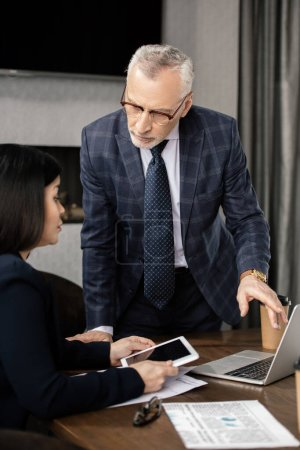 businessman and asian businesswoman with digital tablet talking during business meeting