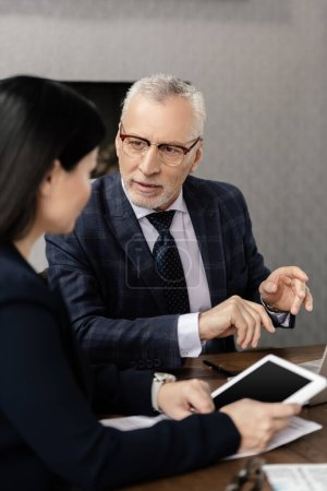 selective focus of businessman talking with businesswoman during business meeting
