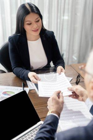 Photo pour Vue en rafale d'un homme d'affaires donnant du papier à une femme d'affaires asiatique souriante pendant une réunion d'affaires - image libre de droit