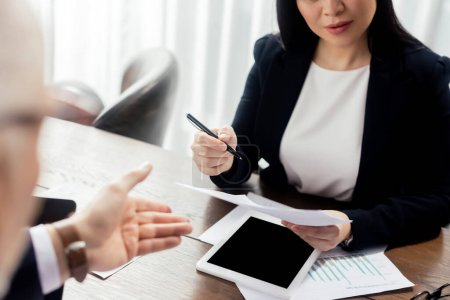 Photo for Cropped view of businessman pointing with hand and businesswoman looking at paper during business meeting - Royalty Free Image