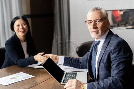 Photo for Selective focus of businessman shaking hands with smiling asian businesswoman during business meeting - Royalty Free Image