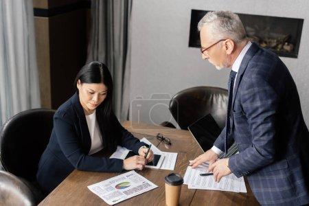 Photo pour Homme d'affaires en costume parler avec asiatique femme d'affaires lors d'une réunion d'affaires - image libre de droit