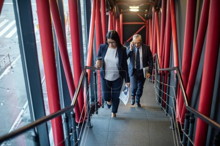 Photo pour Homme d'affaires parlant sur smartphone et asiatique femme d'affaires avec tasse en papier marchant sur les escaliers - image libre de droit
