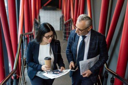 Photo pour Vue grand angle de l'homme d'affaires et asiatique femme d'affaires regardant le journal - image libre de droit