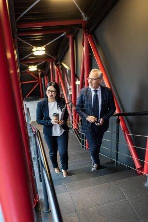 Photo pour Vue en hauteur d'un homme d'affaires souriant et d'une femme d'affaires asiatique parlant et marchant dans les escaliers - image libre de droit