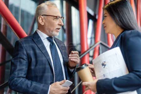 businessman with smartphone and asian businesswoman with paper cup talking and looking at each other