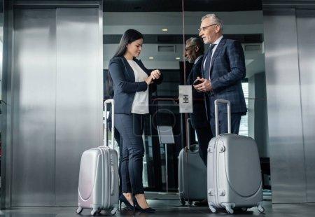Foto de Un hombre de negocios sonriente y una mujer de negocios asiática con bolsas de viaje cerca del ascensor. - Imagen libre de derechos