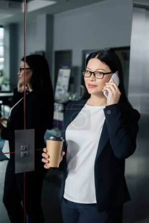 attractive asian businesswoman holding paper cup and talking on smartphone