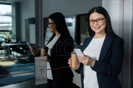 Photo pour Une femme d'affaires asiatique souriante tenant une tasse de papier, un téléphone intelligent et regardant une caméra - image libre de droit
