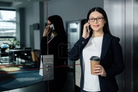 smiling asian businesswoman holding paper cup and talking on smartphone