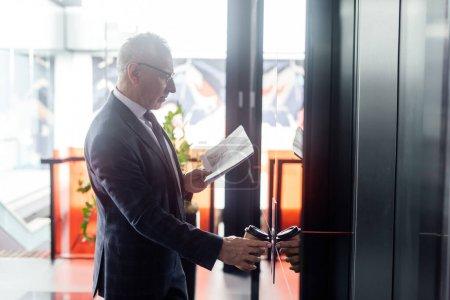 Photo pour Vue latérale de l'homme d'affaires avec journal et papier tasse bouton-poussoir de l'ascenseur - image libre de droit