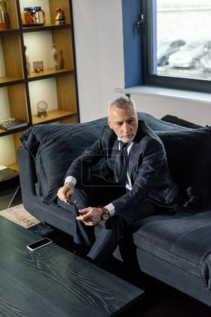 Photo for High angle view of businessman in suit sitting on sofa and holding glasses - Royalty Free Image