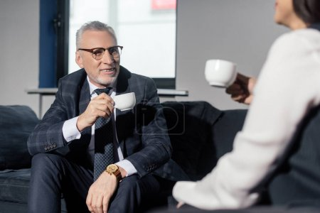 Photo for Selective focus of businessman holding cup and talking with businesswoman - Royalty Free Image