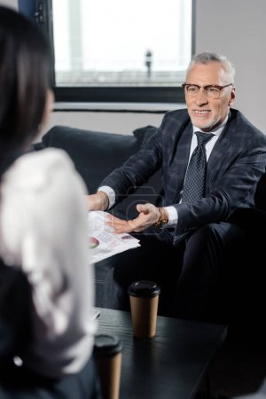 Photo for Selective focus of smiling businessman holding papers and talking with businesswoman - Royalty Free Image