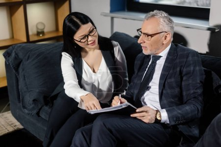 high angle view of businessman and smiling asian businesswoman talking and holding papers