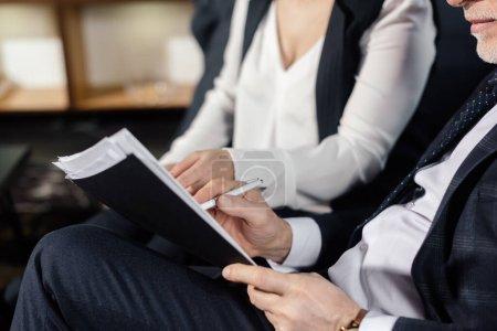 Photo pour Vue recadrée d'un homme d'affaires et d'une femme d'affaires faisant de la paperasse à l'hôtel - image libre de droit