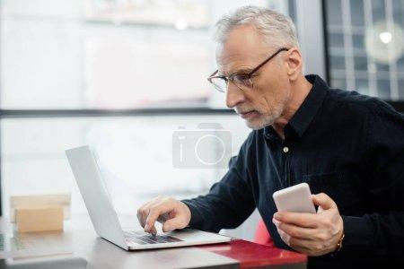Photo pour Bel homme d'affaires tenant smartphone et en utilisant un ordinateur portable dans le café - image libre de droit