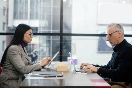 Photo pour Vue latérale d'un homme d'affaires utilisant un ordinateur portable et d'une femme d'affaires asiatique utilisant une tablette numérique dans un café - image libre de droit