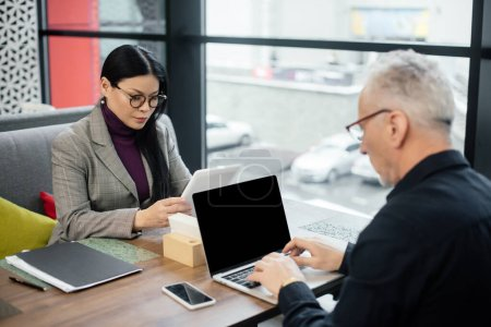 Photo pour Homme d'affaires en utilisant un ordinateur portable et asiatique femme d'affaires en utilisant une tablette numérique dans le café - image libre de droit