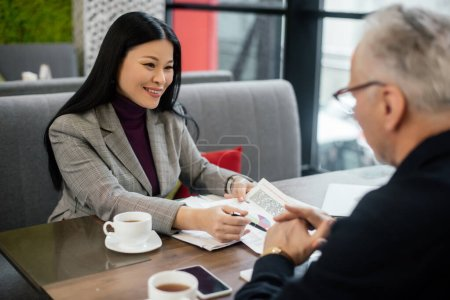 selective focus of smiling asian businesswoman talking with businessman and pointing at papers in cafe