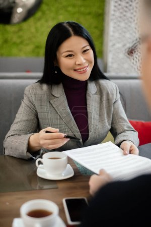 Photo for Selective focus of smiling asian businesswoman talking with businessman and holding papers in cafe - Royalty Free Image