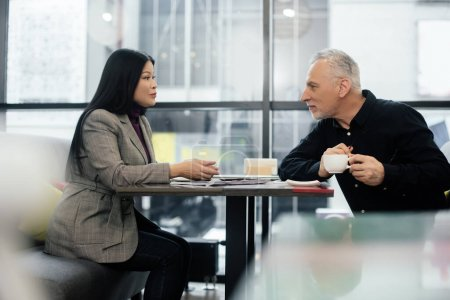 Photo for Side view of businessman and asian businesswoman talking in cafe - Royalty Free Image