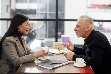 Photo for Side view of businessman and smiling asian businesswoman talking in cafe - Royalty Free Image