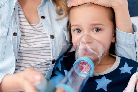 Photo for Selective focus of caring mother holding inhaler with spacer near sick daughter - Royalty Free Image