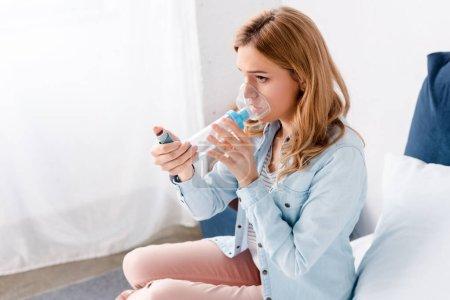 Asthmatikerin mit Inhalator mit Abstandhalter im Schlafzimmer