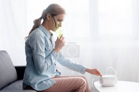Photo pour Vue latérale de la femme en masque respiratoire touchant compresseur inhalateur - image libre de droit