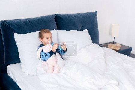 Photo pour Malade enfant en utilisant inhalateur avec entretoise près de lapin jouet - image libre de droit