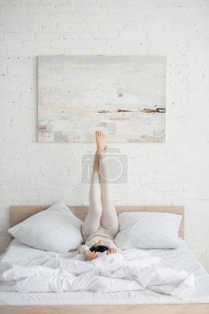 Photo pour Femme aux cheveux colorés et jambes levées couchées sur le lit dans la chambre - image libre de droit