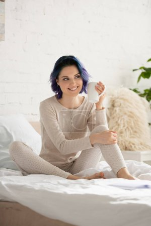 Photo for Girl with colorful hair and cup of tea smiling and sitting on bed in bedroom - Royalty Free Image