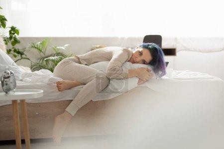 Photo pour Focus sélectif de belle fille aux cheveux colorés couché sur le lit et regardant la caméra dans la chambre - image libre de droit