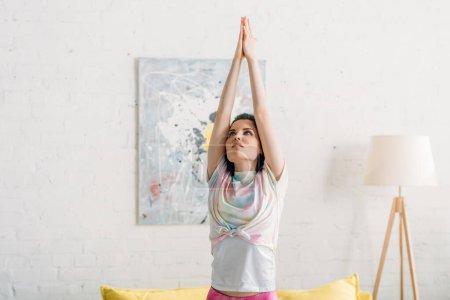 Photo pour Femme aux cheveux colorés et les mains serrées faire du yoga asana dans le salon - image libre de droit