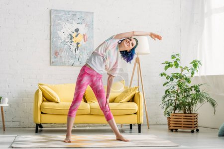 Photo for Girl with colorful hair warming up with outstretched hand and smiling in living room - Royalty Free Image