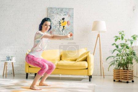 Photo pour Fille avec des cheveux colorés dans la pose de chaise avec les mains tendues en regardant la caméra dans le salon - image libre de droit