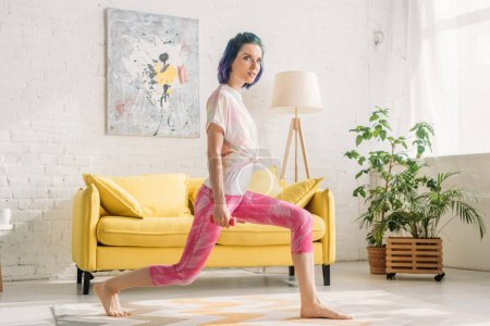 Beautiful girl with colorful hair doing lunges with dumbbell in living room