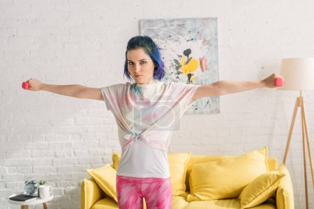 Photo for Woman with colorful hair holding dumbbells with outstretched hands and looking at camera in living room - Royalty Free Image
