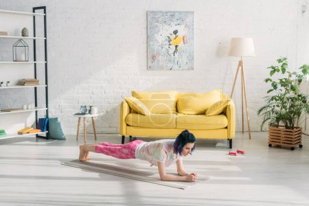 Photo for Girl with colorful hair doing plank on yoga mat near sofa in living room - Royalty Free Image